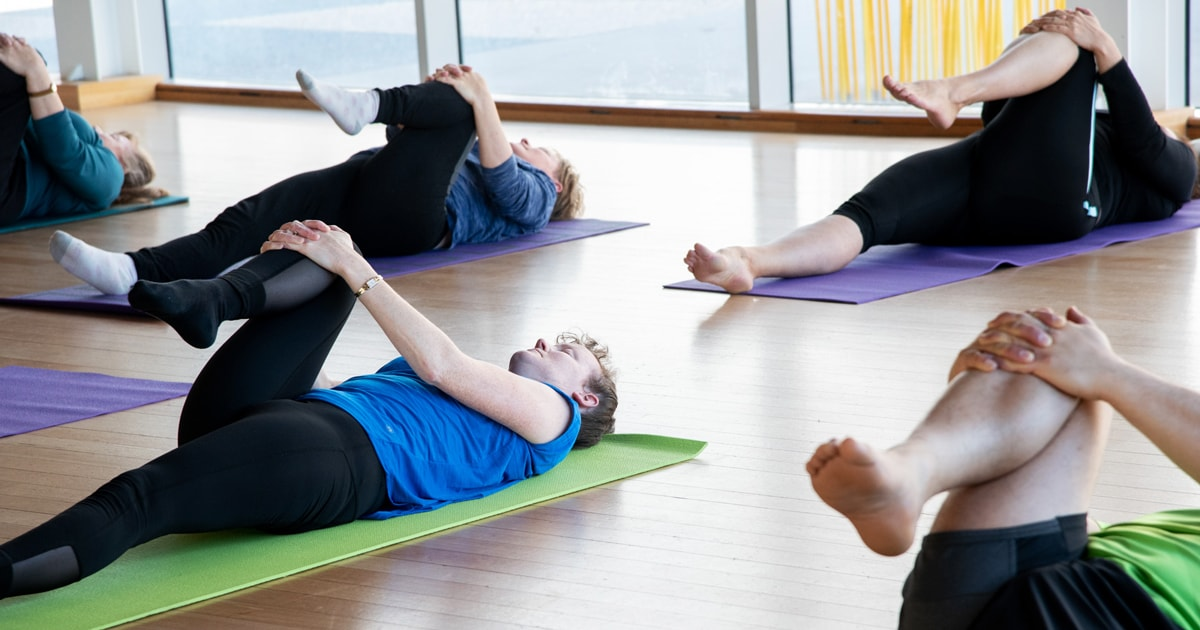 People lie on yoga mats in a dance studio stretching their legs up to their chests