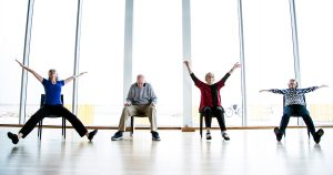 Dance class participants seated in chairs perform dance moves with raised arms