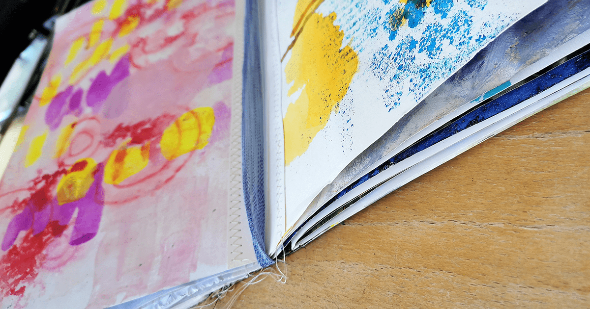 Close up of an artist-created book, with handstitched binding and hand-painted pages