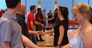 A dance class stands in pairs holding hands as they listen to an instructor
