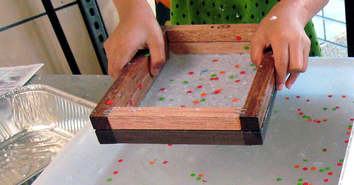 Two hands holding wooden paper making frame over bucket of water with colourful confetti