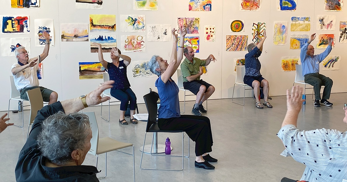 Dance class participants perform a seated dance in a gallery space