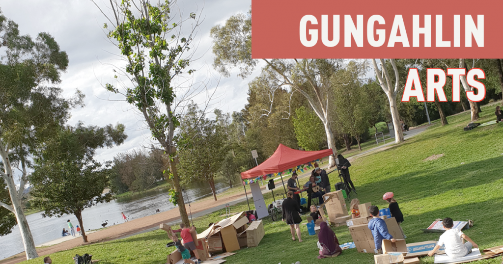 Musicians are playing in a marquee in front of Yerrabi pond while children play with cardboard boxes in the foreground.  The text 'Gungahlin Arts' is at the top of the image.