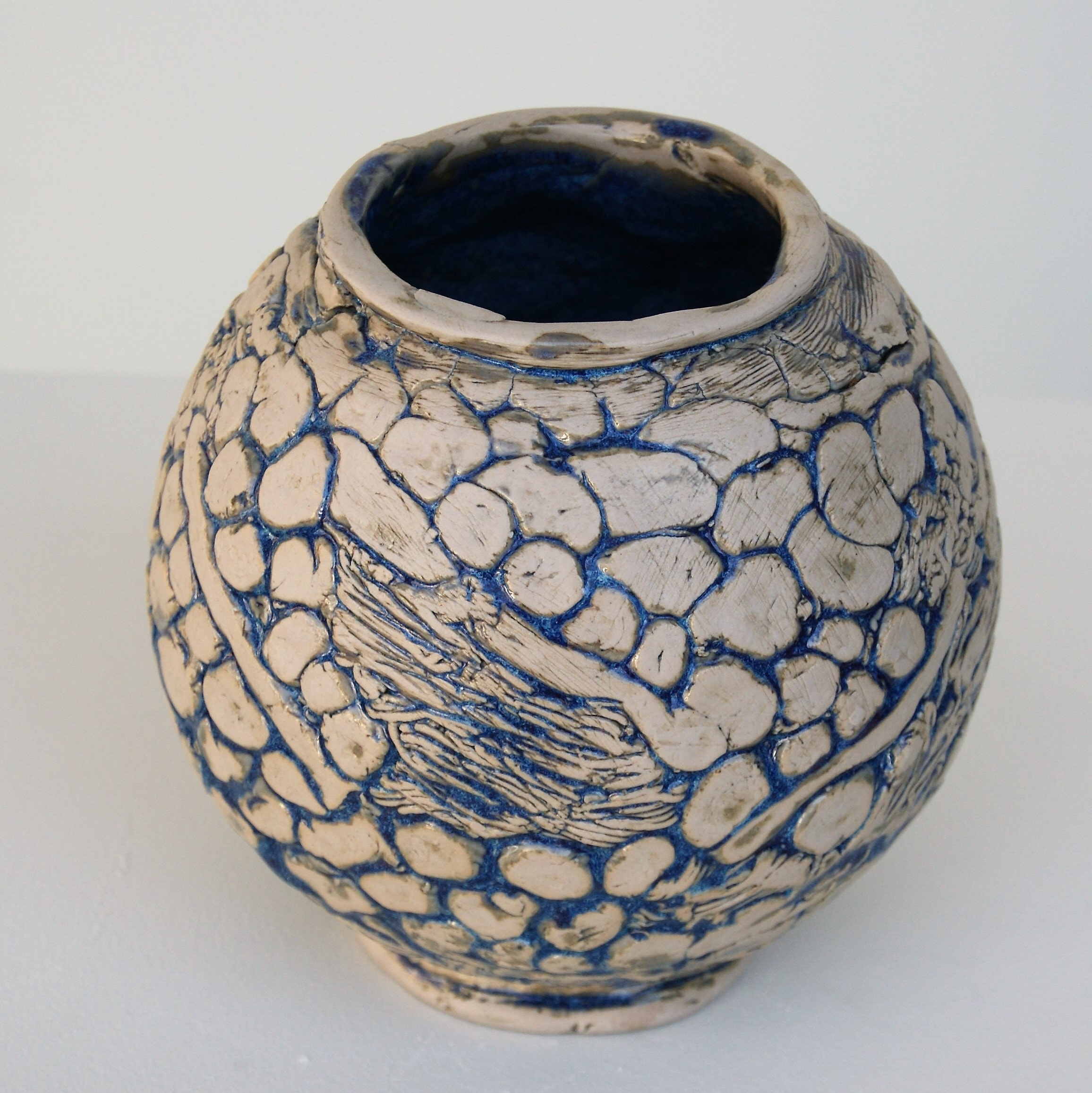 Large spherical hand-built pot in pale ceramic body featuring patterns created with dots, lines and textures accentuated with touches of blue glaze.