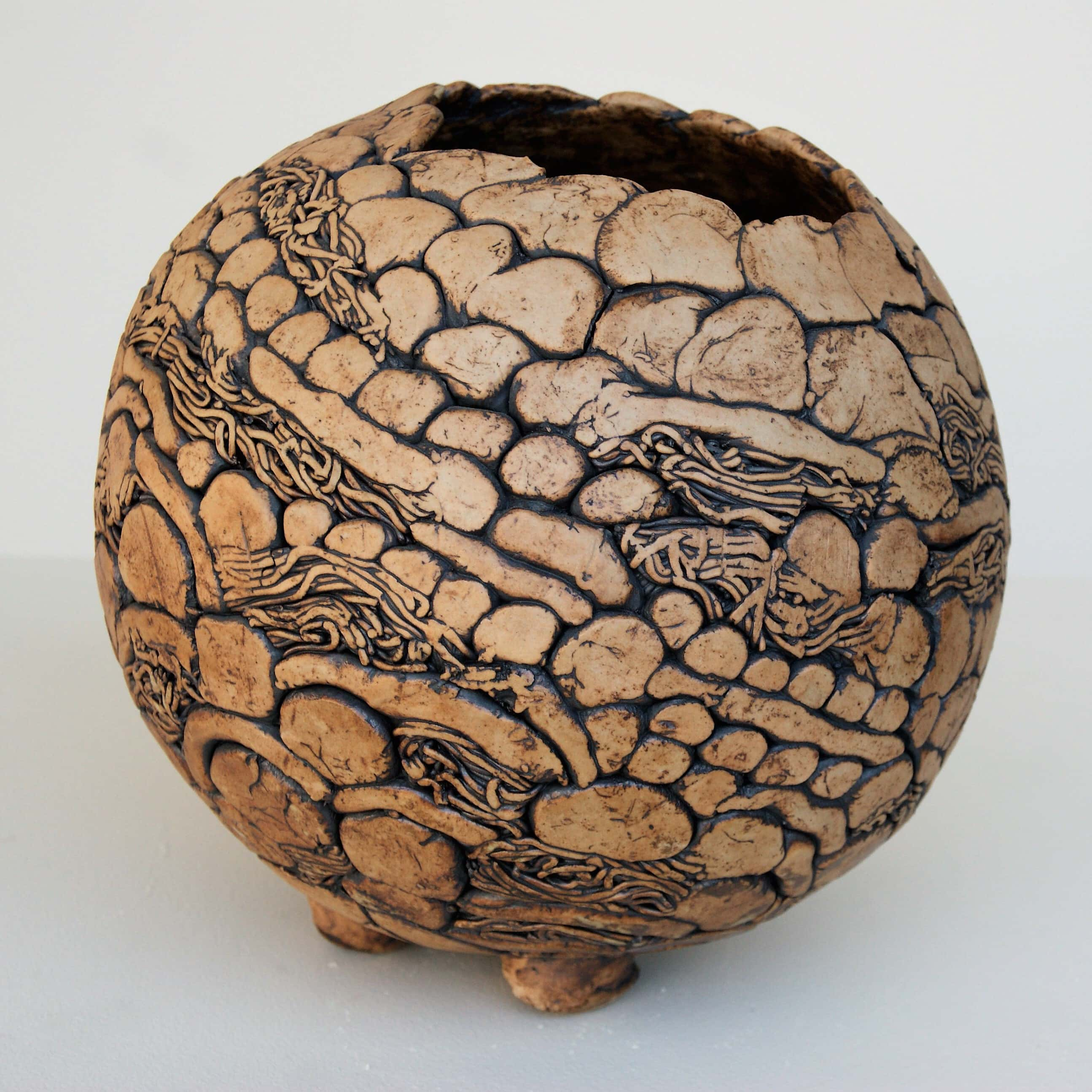 Hand-built, three footed pot featuring coiled surface patterning made using dots, lines and textures with an asymmetrical opening on top.