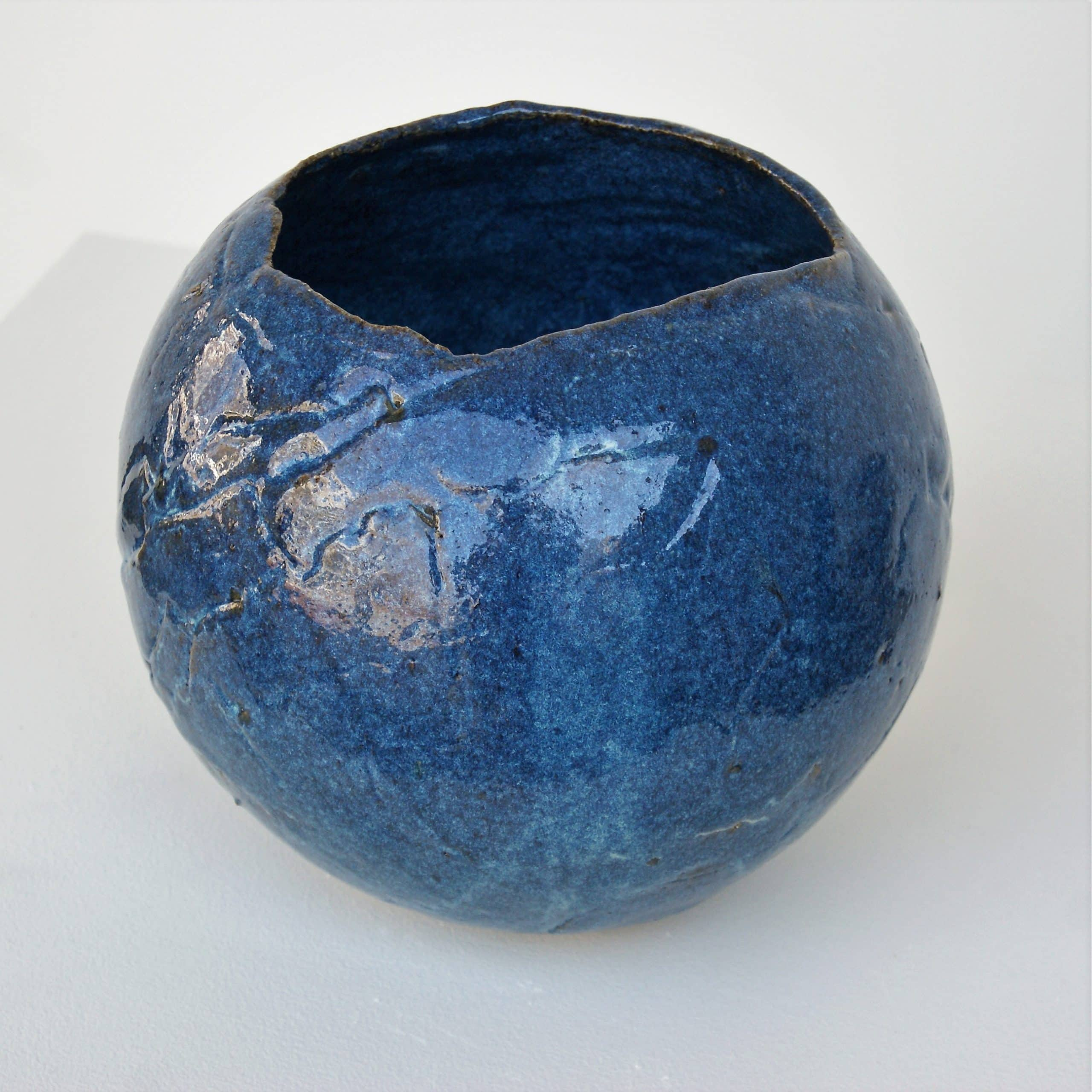 Large, slab-built spherical pot with asymetrical opening on top, glazed in blue.