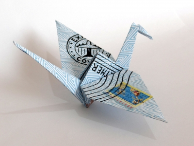 Digital image of an origami crane folded from paper featuring a multicoloured lino print of an envelope pattern and postage marks, with a selected stamp visible on the wing.