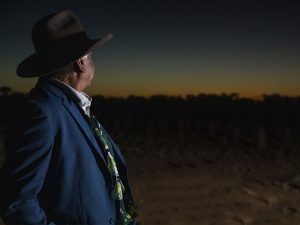 An Indigenous man looks into the distance where the sun sets on the horizon