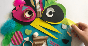 A stylised bird made of cut-out cardboard, paper and feathers