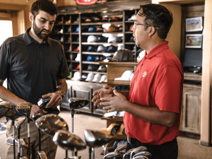 Two men stand next to a cart of golf clubs having a conversation