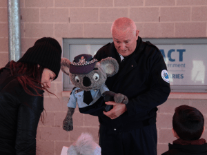 A policeman holds a koala puppet dressed in police uniform