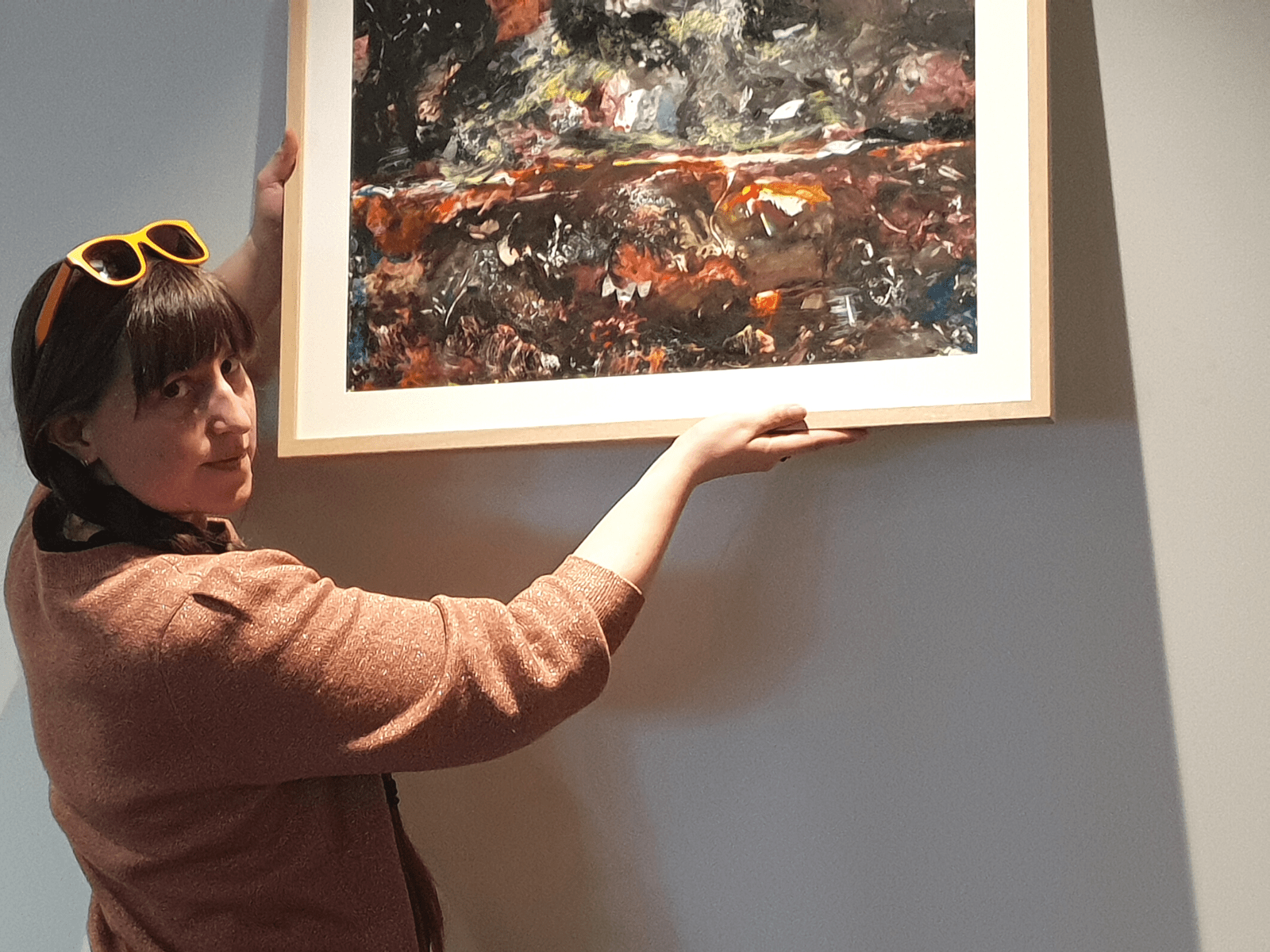A woman holds a framed painting up against a wall as she looks back at the camera