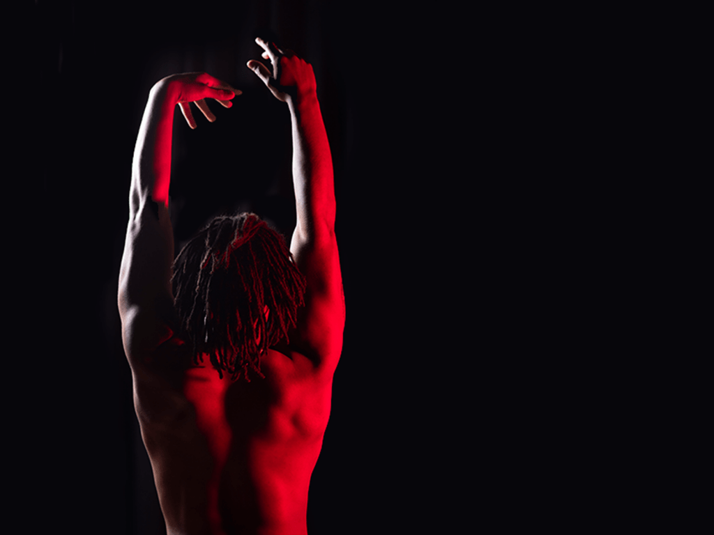 A man lit by red light stands with his back to the camera and arms stretched above his head in a darkened space