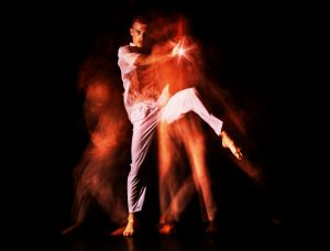 A man dances against a black background as mist swirls around him and a bright light shines from his right hand